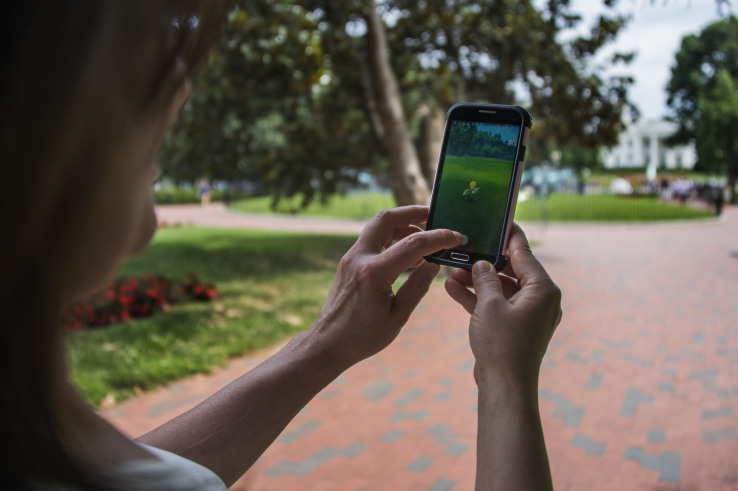"""A woman holds up her cell phone as she plays the Pokemon Go game in Lafayette Park in front of the White House in Washington, DC, July 12, 2016. Pokémon Go mania is sweeping the US as players armed with smartphones hunt streets, parks, rivers and elsewhere to capture monsters and gather supplies in the hit game. The free application based on a Nintendo title that debuted 20 years ago has been adapted to the mobile internet Age by Niantic Labs, a company spun out of Google last year after breaking ground with an """"Ingress"""" game that merged mapping capabilities with play. As of July 11, 2016 Pokémon Go had been downloaded millions of times, jumping topping rankings at official online shops for applications tailored for smartphones powered by Apple or Google-backed Android software.  / AFP / JIM WATSON        (Photo credit should read JIM WATSON/AFP/Getty Images)"""